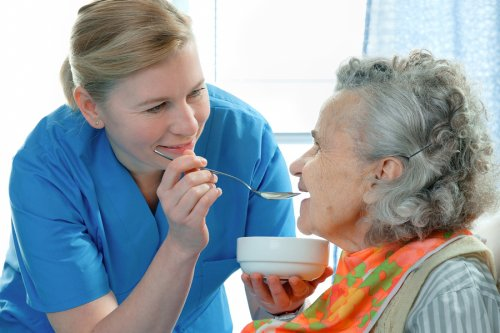 Nurse feeding an elderly woman